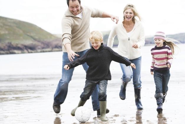 rodzice biegają z dziećmi po plaży