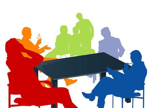 grupa ludzi rozmawia przy stole