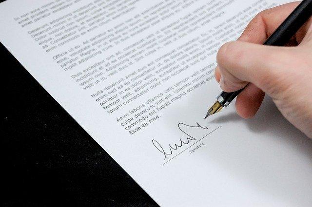 osoba podpisuje jakiś dokument