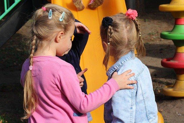 dwie dziewczynki na placu zabaw rozmawiają ze sobą, w tle zjeżdżalnia