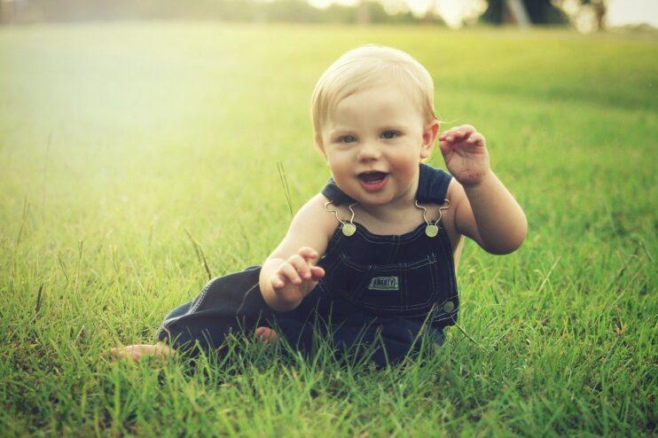 dziecko siedzi na łące i uśmiecha się